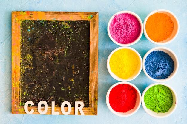 Colore del testo su ardesia di legno con polvere di colore holi nelle ciotole bianche Foto Gratuite