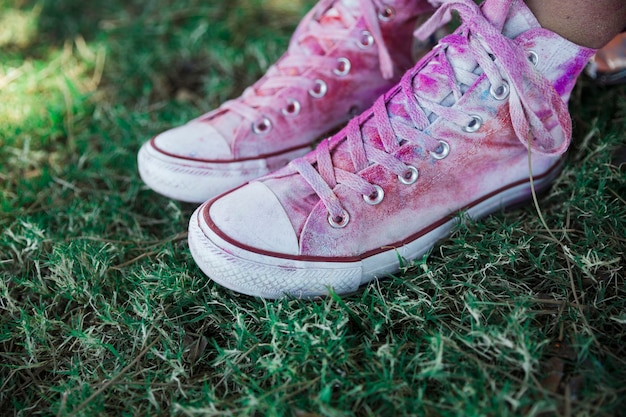 Colore holi sopra le scarpe di tela bianca sull'erba verde Foto Gratuite