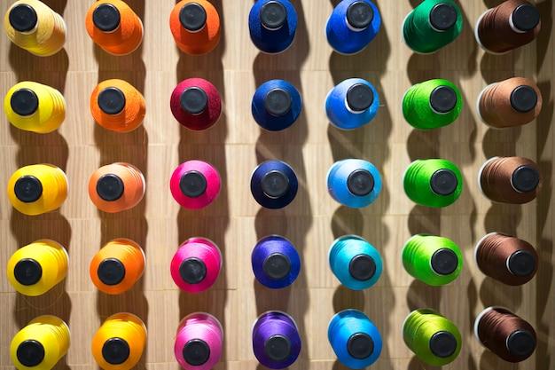 Colori assortiti di filo sui rulli. processo di ricamo in fabbrica. Foto Premium