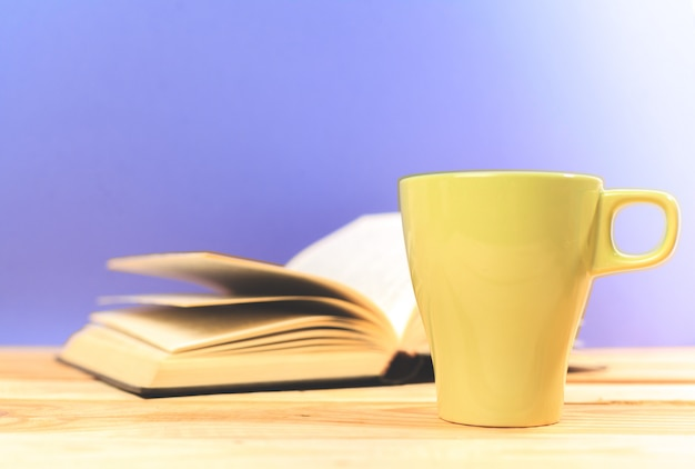 Colori la tazza di tè con i libri sulla tavola Foto Premium