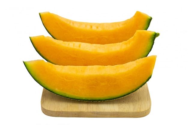 Colori luminosi del melone del primo piano che è pezzi sul vassoio di legno isolato su fondo bianco. Foto Premium