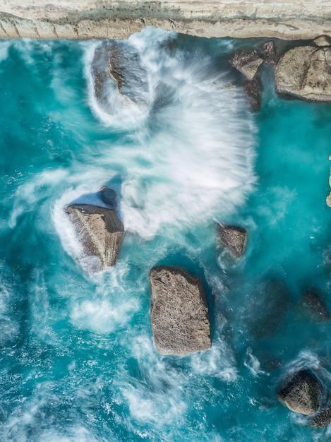 Colpo ambientale verticale delle formazioni rocciose sul corpo del mare blu Foto Gratuite