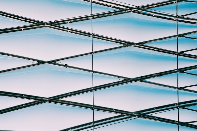 Colpo basso angolo di cavi metallici geometrici su un edificio di vetro Foto Gratuite