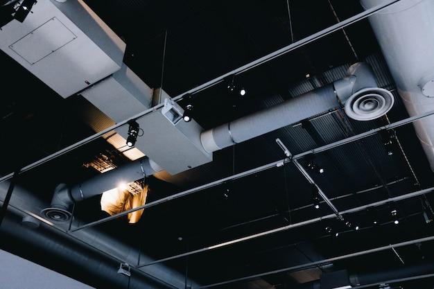 Colpo basso angolo di un soffitto di metallo nero con tubi di ventilazione bianchi Foto Gratuite