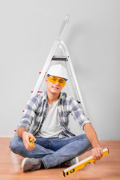 Colpo completo dell'operaio che si siede vicino ad una scala Foto Gratuite