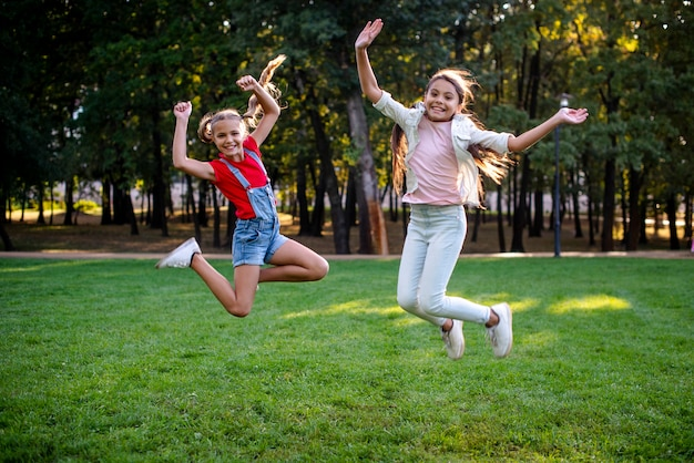 Colpo completo delle ragazze che saltano all'aperto Foto Gratuite