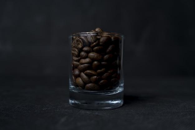 Colpo del primo piano dei chicchi di un bicchiere di caffè su una superficie scura Foto Gratuite