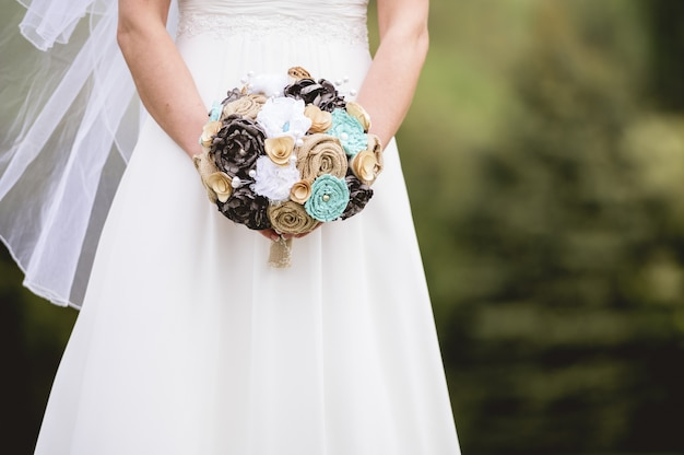 Colpo del primo piano della sposa che tiene un mazzo di fiori Foto Gratuite