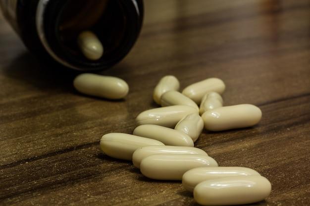 Colpo del primo piano delle capsule bianche della medicina su una superficie di legno Foto Gratuite