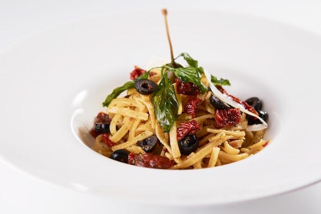 Colpo del primo piano di pasta con frutta secca, olive e menta su un muro bianco Foto Gratuite