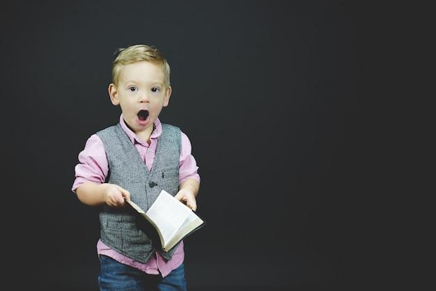 Colpo del primo piano di un bambino sorpreso che tiene la bibbia Foto Gratuite