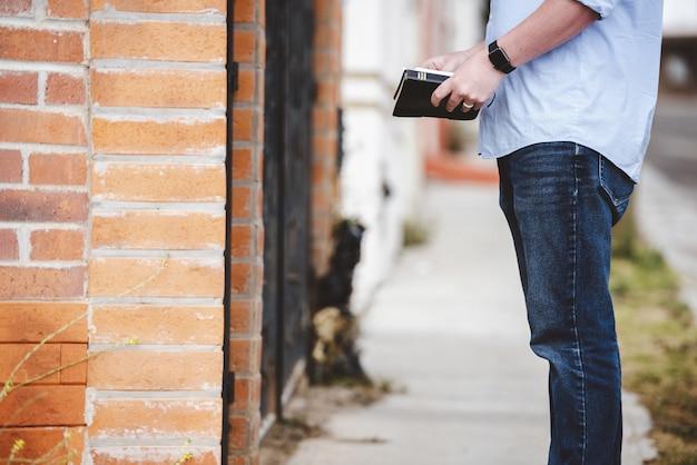 Colpo del primo piano di un maschio che sta vicino ad una costruzione mentre tenendo la bibbia Foto Gratuite
