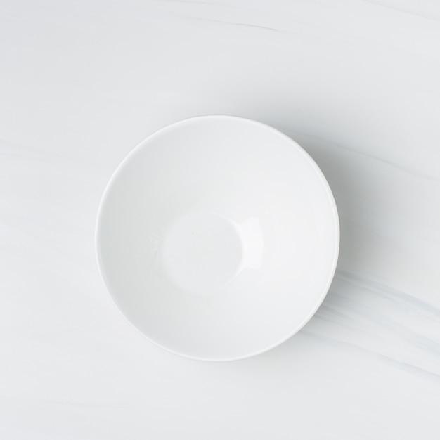 Colpo del primo piano di una ciotola di ceramica bianca vuota su una parete bianca Foto Gratuite