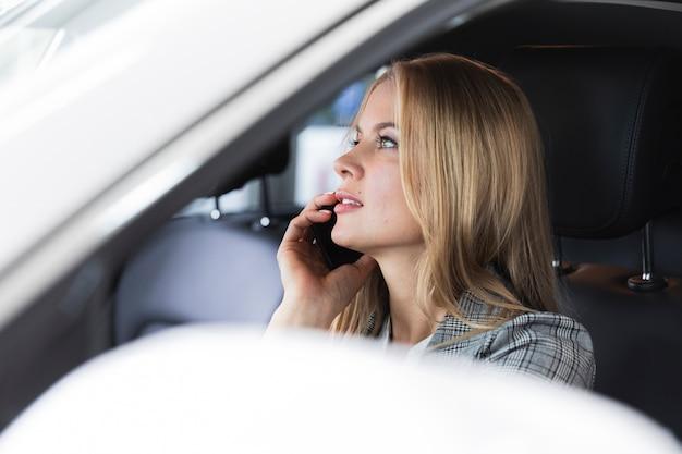 Colpo del primo piano di una donna bionda che parla al telefono Foto Gratuite