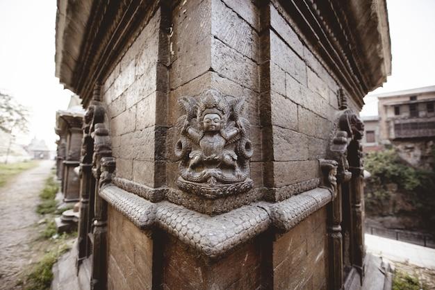 Colpo del primo piano di una parete con scolpire in un tempio indù in nepal Foto Gratuite