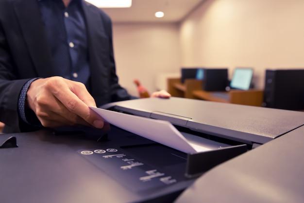 Colpo del primo piano gli uomini d'affari hanno messo la carta nel vassoio della fotocopiatrice. Foto Premium