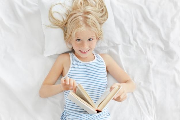 Colpo dell'interno della bambina adorabile allegra con capelli biondi che si trovano sul cuscino bianco nella sua camera da letto, godendo leggendo favola. carino bambina dagli occhi azzurri che legge invece di fare un sonnellino, con uno sguardo furbo Foto Gratuite