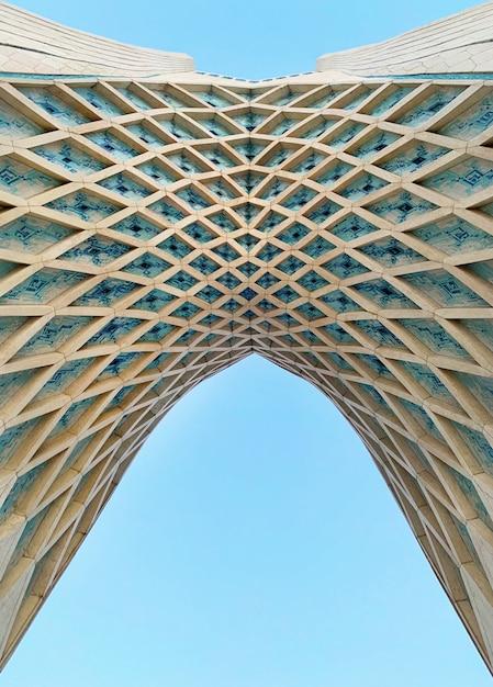 Colpo di angolo basso dell'arco della torre di azadi a teheran con cielo blu Foto Gratuite