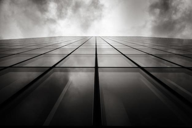 Colpo di angolo basso di gradazione di grigio di un grattacielo una parete con le finestre di vetro sotto il cielo nuvoloso Foto Gratuite