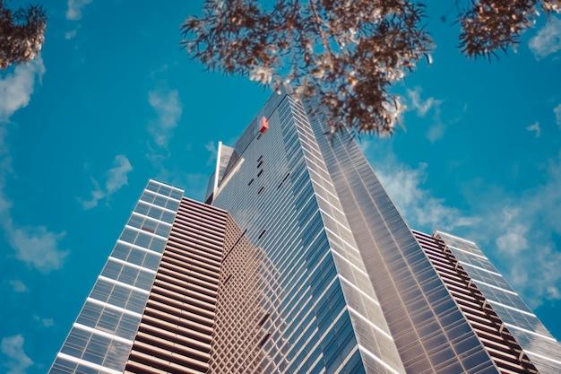 Colpo di angolo basso di un edificio alto business con un cielo nuvoloso blu Foto Gratuite