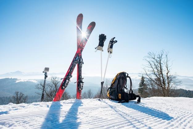 Colpo di attrezzatura da sci - sci, zaino, bastoncini, guanti e action camera su monopiede Foto Premium