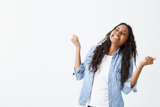 Colpo di donna di successo dalla pelle scura con lunghi capelli ondulati che indossa una camicia di jeans stringendo i pugni con eccitazione essendo felice di celebrare il suo successo e successo. Foto Gratuite