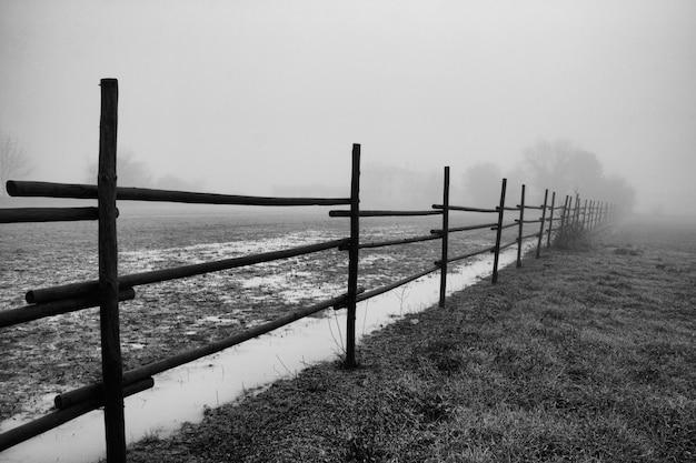 Colpo di gradazione di grigio di una rete fissa in un campo in mugla in turchia durante il tempo nebbioso Foto Gratuite