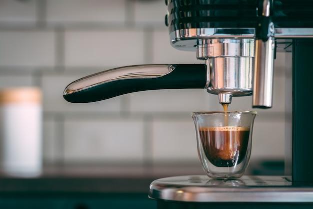 Colpo di messa a fuoco selettiva di una macchina per caffè espresso che produce gustoso caffè caldo al mattino Foto Gratuite