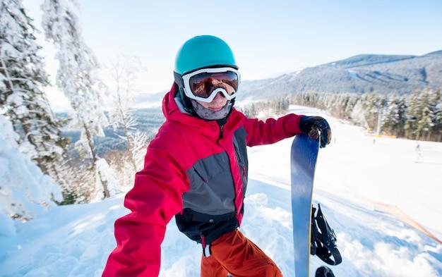 Colpo di un uomo snowboarder prendendo un selfie, in piedi sul pendio della collina presso la stazione sciistica in una bella giornata di sole invernale presso la stazione sciistica bukovel in montagna Foto Premium