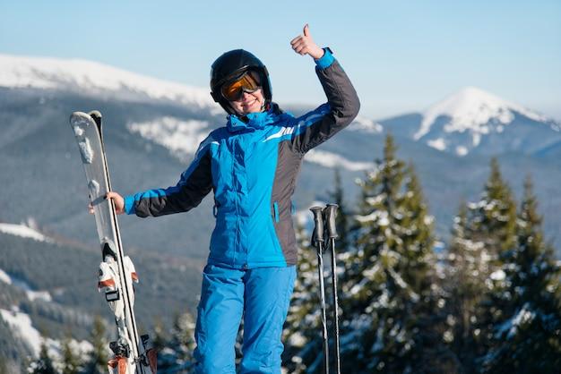 Colpo di una femmina felice, sorridente, mostrando i pollici in posa in montagna godendo la sua vacanza presso la stazione sciistica Foto Premium
