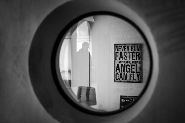 Colpo in scala di grigi di un segno di citazione motivazionale sul muro visto attraverso una finestra rotonda Foto Gratuite