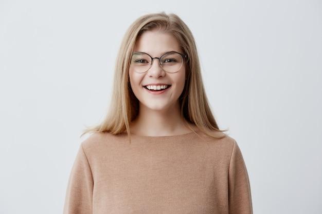 Colpo in testa di giovane donna caucasica dall'aspetto piacevole che indossa gli occhiali con il grande sorriso che mostra i suoi denti bianchi diritti essere felici a causa delle notizie positive. ragazza bionda con un sorriso piacevole Foto Gratuite