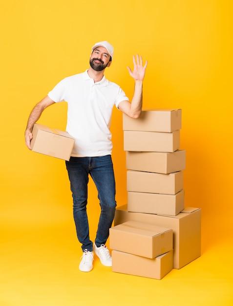 Colpo integrale del fattorino fra le scatole sopra il saluto giallo isolato con la mano con l'espressione felice Foto Premium