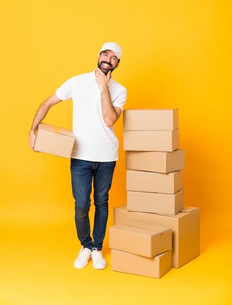 Colpo integrale del fattorino fra le scatole sopra sorridere giallo isolato del fondo Foto Premium