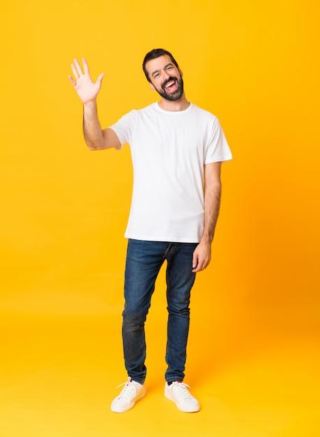 Colpo integrale dell'uomo con la barba sopra fondo giallo isolato che saluta con la mano con l'espressione felice Foto Premium