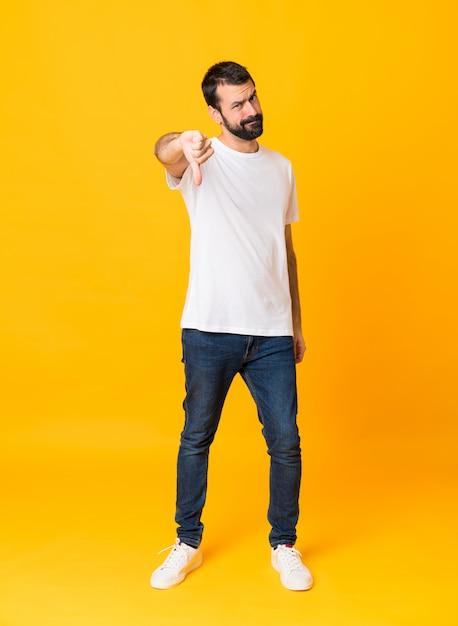 Colpo integrale dell'uomo con la barba sopra il pollice di mostra giallo isolato giù con l'espressione negativa Foto Premium