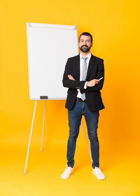 Colpo integrale dell'uomo d'affari che dà una presentazione sul bordo bianco sopra fondo giallo isolato Foto Premium
