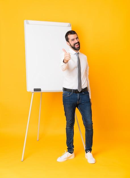 Colpo integrale dell'uomo d'affari che dà una presentazione sul bordo bianco sopra giallo isolato con i pollici su Foto Premium