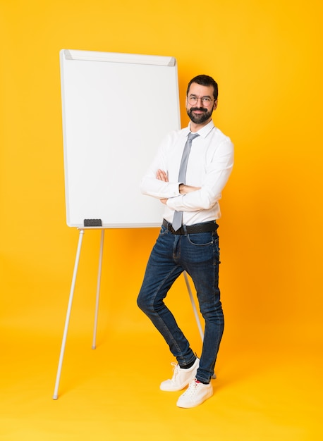 Colpo integrale dell'uomo d'affari che dà una presentazione sul bordo bianco sopra giallo isolato con i vetri e sorridere Foto Premium