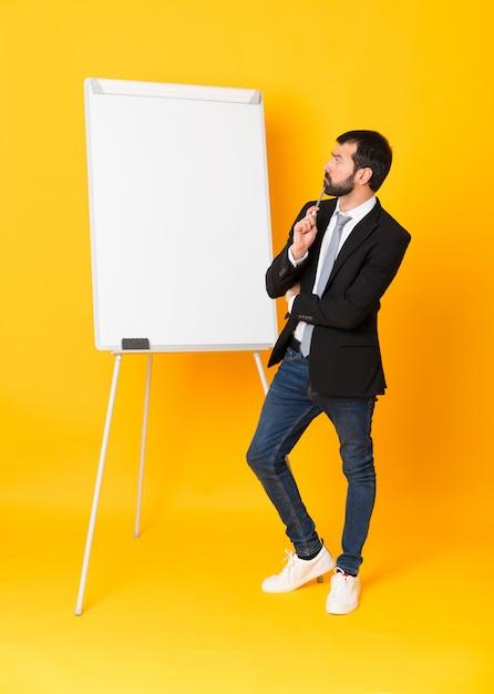 Colpo integrale dell'uomo d'affari che dà una presentazione sul bordo bianco sopra giallo isolato Foto Premium