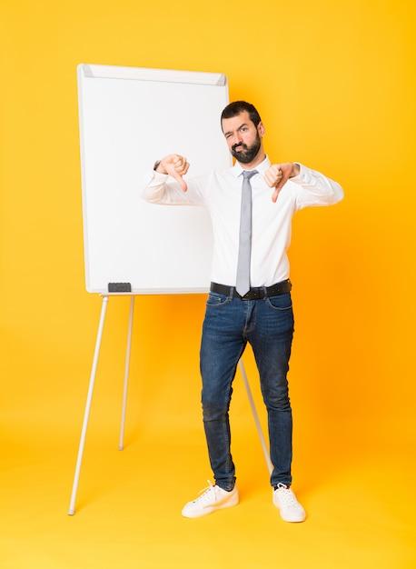 Colpo integrale dell'uomo d'affari che dà una presentazione sul bordo bianco sopra il pollice di mostra giallo isolato giù Foto Premium