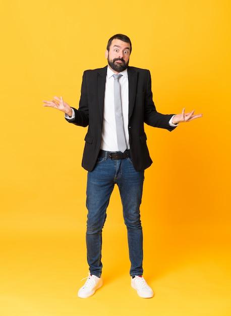 Colpo integrale dell'uomo di affari sopra fondo giallo isolato che fa gesto di dubbi Foto Premium
