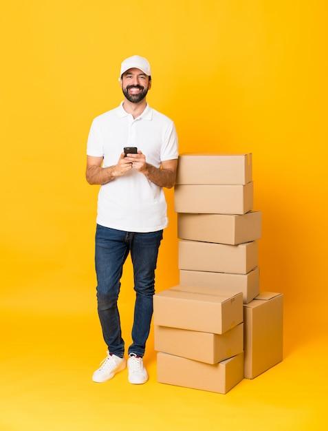 Colpo integrale dell'uomo di consegna fra le scatole sopra la parete gialla isolata che invia un messaggio con il cellulare Foto Premium