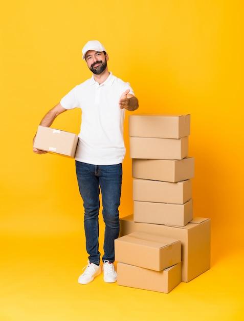 Colpo integrale dell'uomo di consegna fra le scatole sopra le mani stringere gialle isolate per chiudere molto Foto Premium