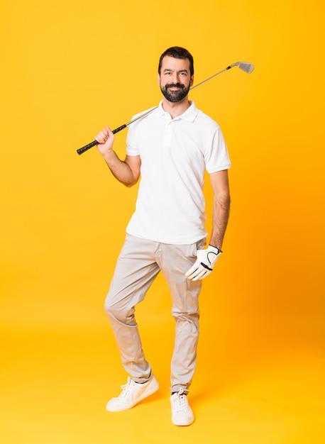 Colpo integrale dell'uomo sopra la parete gialla isolata che gioca golf Foto Premium