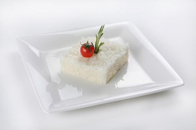 Colpo isolato di un riso a forma di quadrato su un piatto bianco Foto Gratuite