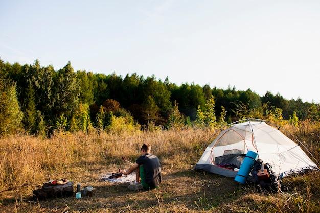 Colpo lungo dell'uomo che esamina la foresta accanto alla sua tenda Foto Gratuite