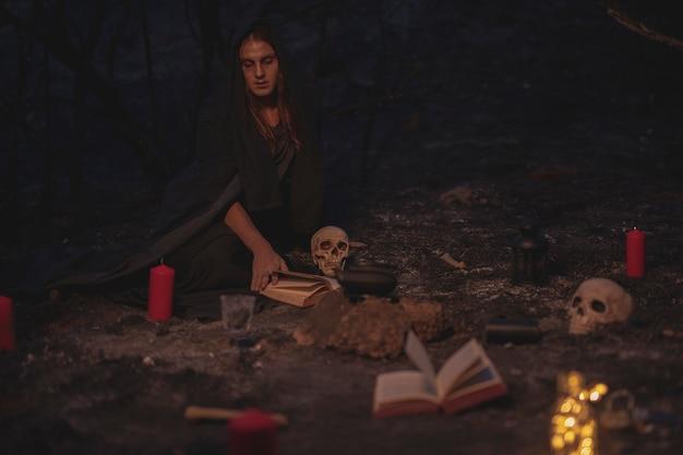 Colpo lungo della disposizione della stregoneria con il libro degli incantesimi e le candele Foto Gratuite