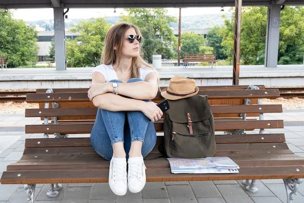 Colpo lungo della donna che si siede su un banco Foto Gratuite