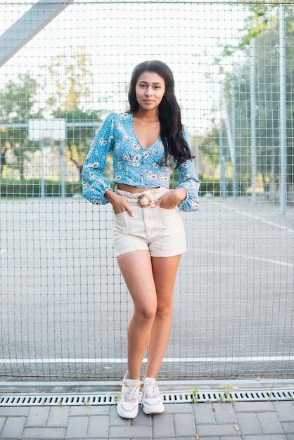 Colpo lungo della donna in piedi accanto a un campo da basket Foto Gratuite